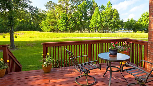 backyard house deck with a table and two chairs overlooking a yard